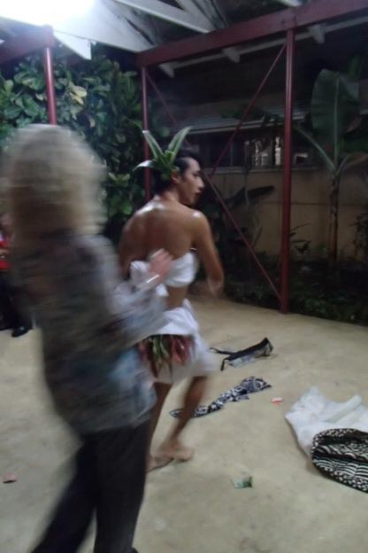 Lesley placing money on Malakai's shiny coconut oil torso.