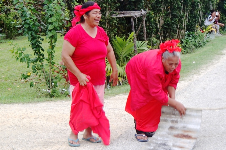 Two lovely ladies out in a village celebrating the Tongan win against the Cook Islands by wearing red and bashing a piece of old tin to drivers!